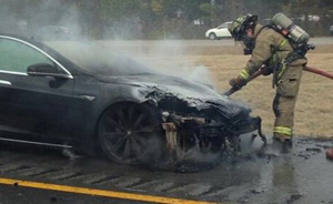 A fire officer extinguishes flames after a Model S hit a large piece of metal in the Road, Louisiana